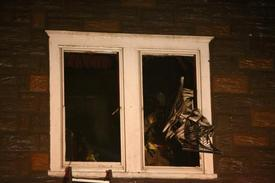 Lt. Matthew Valocchi throws burnt debris from the 2nd floor window of the home that caught on fire on Maple Ave.