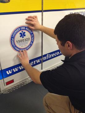 Berwyn EMS Lieutenant Scott Kramer proudly displays our Department of Health licensure seals on the new ambulance.