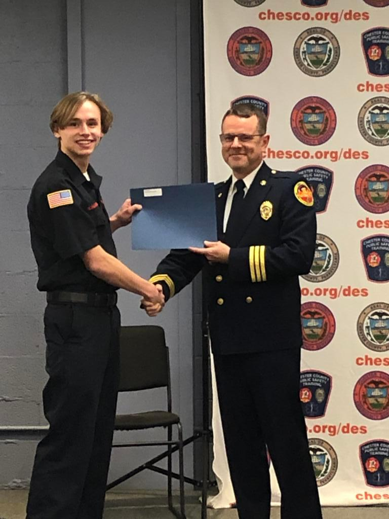 Firefighter Nicholas Sondergaard receiving his certificate from Deputy Chief Justin Brundage.