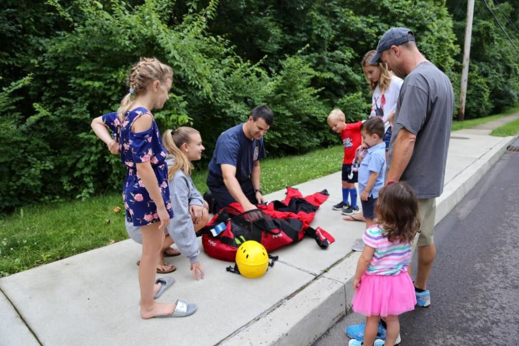 Firefighter/EMT Bryan Humbarger showing his family and neighbors his water rescue equipment.