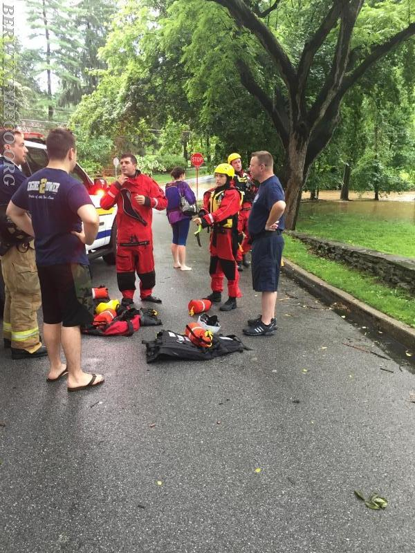 Rescuers debrief after rescuing one occupant from their vehicle along Trout Creek in the Glenhardie section of Tredyffrin Township on June 24, 2017.