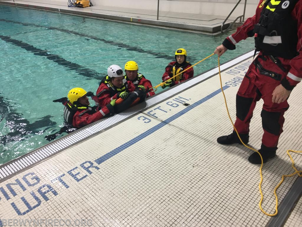 "Members using a FAST Rescue Board to remove a simulated patient from a hole in the ice with the edge of the pool acting as an ""ice mantel""."