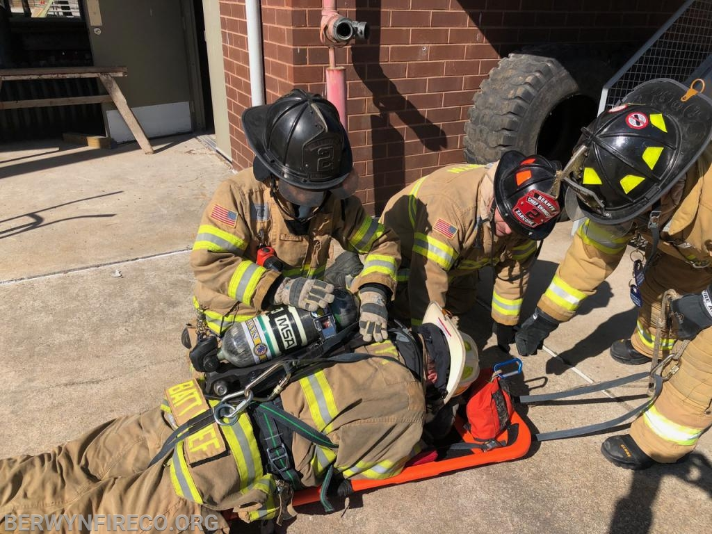 Packaging a firefighter for movement up a set of stairs. This simulates removing a downed firefighter from a basement. One of the most challenging and dangerous situations in firefighter rescue.