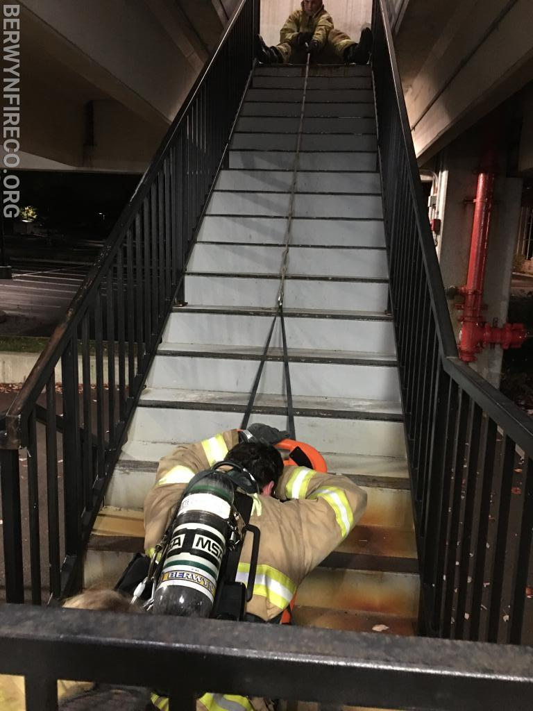 Movement of a downed firefighter up a set of steps.