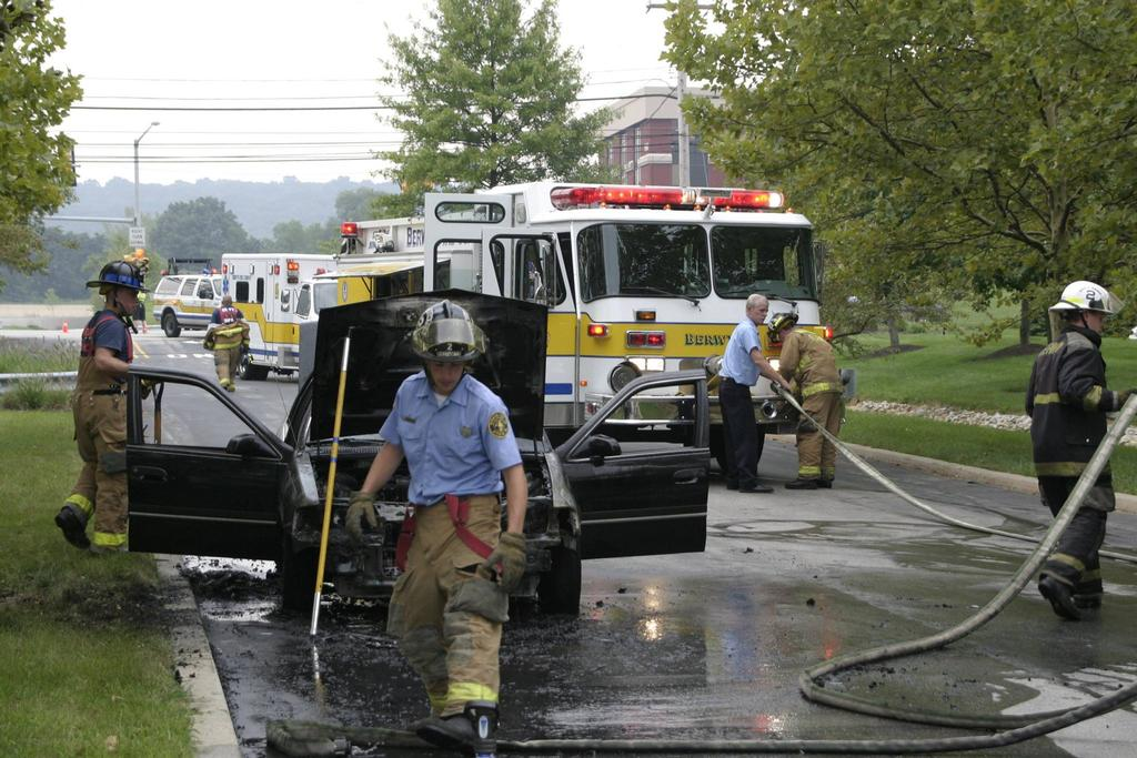 Charlie repacking hose on Engine 2-0 after a car fire at the Bay Colony Executive Park in Tredyffrin Township on August 11, 2004.